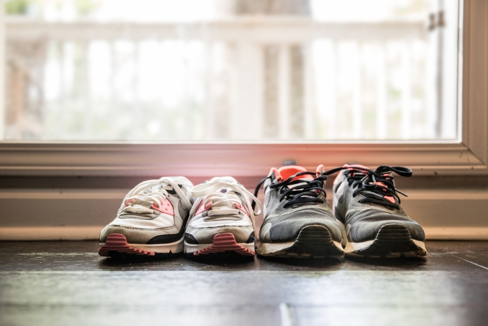 Two pairs of sneakers on a tile floor