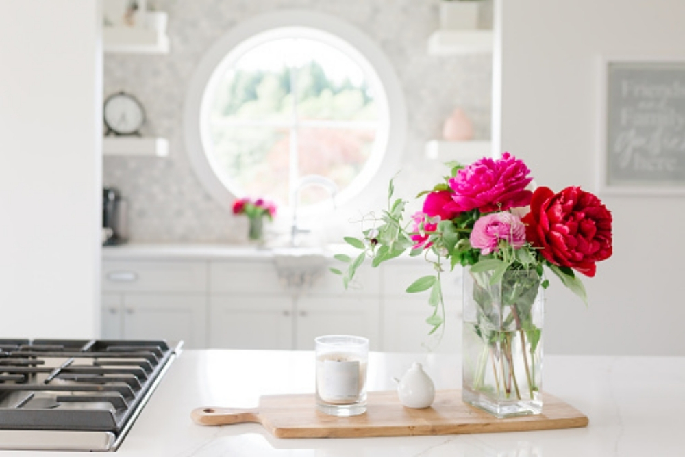A pink bouquet of flowers and a candle in a bright white kitchen